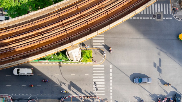 Draufsichtantenne eines treibenden autos auf asphaltbahn und fußgängerzebrastreifen in der verkehrsstraße mit licht- und schattenschattenbild mit schienenhimmelzug.