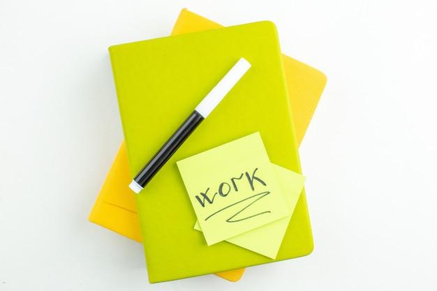 Draufsichtarbeit auf grüner haftnotiz mit schwarzem marker auf bunten notizbüchern auf weiß geschrieben