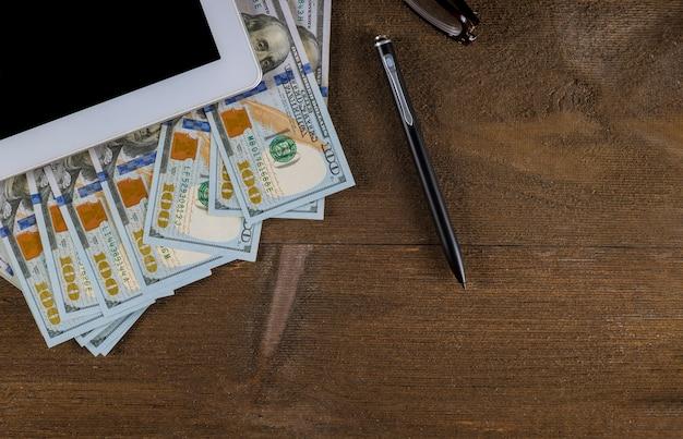 Draufsichtarbeitsplatz mit gelddollarscheinen und stift auf holztischhintergrund