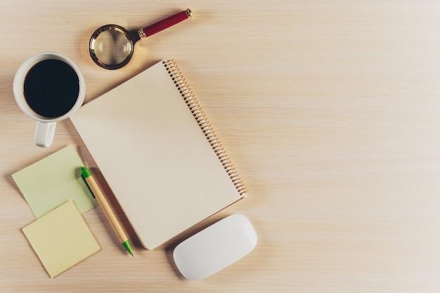 Draufsichtarbeitsplatz mit leerem notizbuch und stift auf holztisch