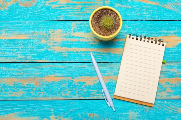 Draufsichtarbeitsplatz mit leerem notizbuch und stift auf holztischhintergrund