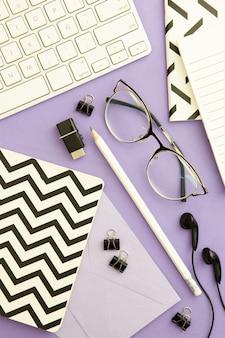 Draufsichtarbeitsplatzanordnung auf purpurrotem hintergrund