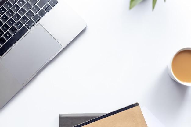 Draufsichtarbeitsplatzlaptop auf weißer tabelle mit kaffeetasse und notizbuch auf hintergrund