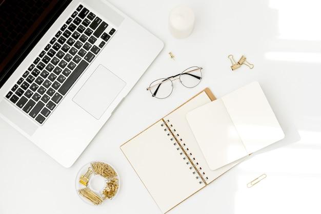 Draufsichtarbeitsplatzmodell auf weiß mit notizbuch, zubehör, kerze und gläsern