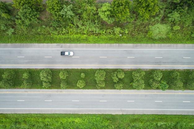 Draufsichtasphaltstraße mitten in grünen jungen reisfeldern