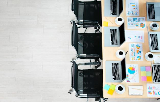 Draufsichtaufnahme des konferenztischs in einem leeren büroraum des unternehmens voller laptop-computer schwarzer heißer kaffee in weißen tassen berichten von datenpapieren und schwarzen stühlen mit kopienraum.