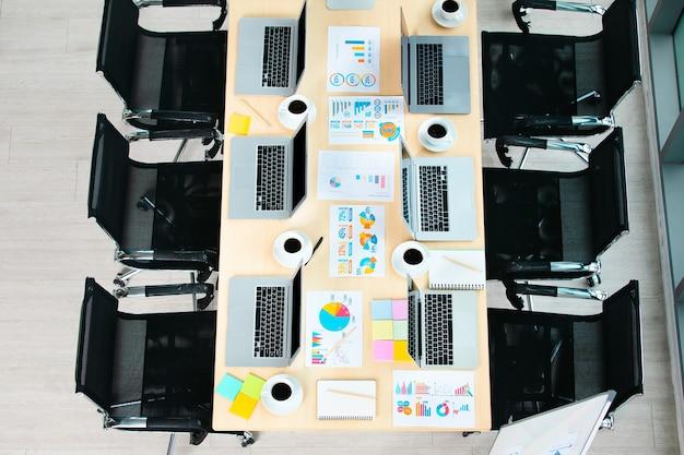 Draufsichtaufnahme des konferenztischs in einem leeren büroraum des unternehmens voller laptop-computer schwarzer heißer kaffee in weißen tassen berichten von datenpapieren und schwarzen stühlen.