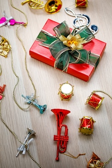 Draufsichtaufnahme einer kleinen roten papierverpackten geschenkbox mit grün-goldener, glänzender bandfliege auf einem holztisch mit kleinen dekorativen musikinstrumenten an heiligabend oder neujahrsfest.