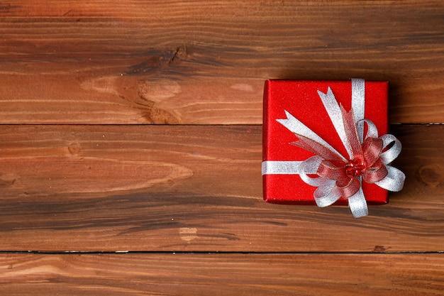 Draufsichtaufnahme einer kleinen roten papierverpackten geschenkbox mit silberglänzender, glänzender bandfliege auf einem alten holztisch mit dunklem muster auf der geburtstagsfeier von frohe weihnachten oder dem neujahrsfest.