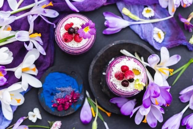 Draufsichtaufnahme einer schönen anzeige der lila veganen smoothies, die mit bunten blumen geschmückt werden