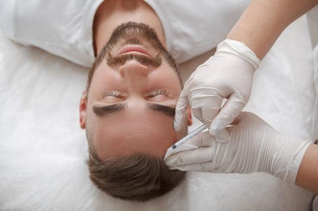 Draufsichtaufnahme eines bärtigen mannes, der haarausfallbehandlung in injektionen durch kosmetikerin erhält