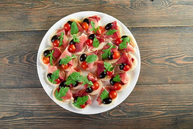 Draufsichtaufnahme eines großen tellers der schinken-häppchen, die mit den schwarzen oliven der kirschtomaten und den rucola-blättern verziert werden, die auf einem hölzernen tisch serviert werden.
