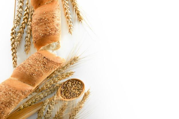 Draufsichtaufnahme eines köstlichen frischen baguettes mit hirse und weizen einzeln auf weißen exemplarbestandteilen natürliches rezept backen gebäck teigeating lebensmittelfrühstück französisches konzept.