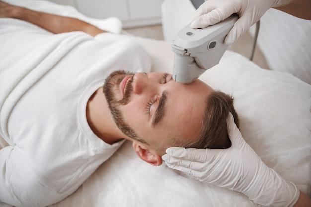 Draufsichtaufnahme eines mannes, der gesichtsbehandlung durch kosmetikerin erhält