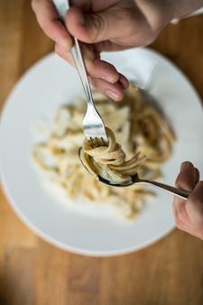 Draufsichtaufnahme eines mannes, der köstliche spaghetti auf einer gabel wirbelt