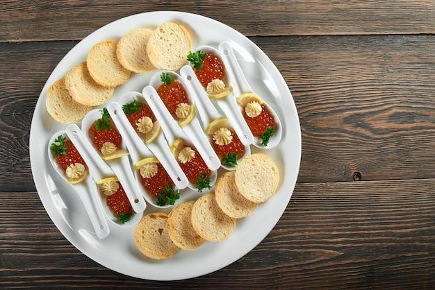 Draufsichtaufnahme eines tellers mit portionen des roten kaviars und der knusprigen zwiebacke auf dem hölzernen tischnahrungsnahrungsessen-essdekorationsrestaurantcafé-cafeteria-menü bestellen luxus-lifestyle-konzept.