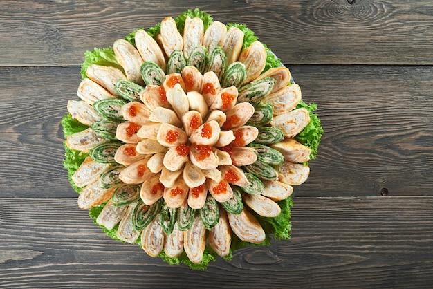 Draufsichtaufnahme eines tellers voller pfannkuchenröllchen mit sahnefüllung, verziert mit rotem kaviar, serviert auf holztisch im restaurant copyspace lebensstil, der lebensmittelzutaten isst, die köstlich kochen.