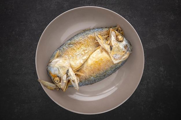 Draufsichtaufnahme von gebratener makrele in keramikplatte auf dunkelgrauem texturhintergrund