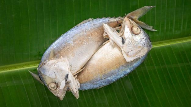 Draufsichtaufnahme von gedämpfter makrele auf grünem bananenblatt-texturhintergrund
