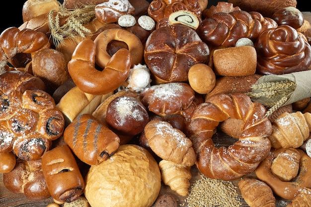Draufsichtaufnahme von köstlichen broten und verschiedenen brötchen, die auf dem tisch gestapelt sind, essen, ernährung, diät, backen, bio-bäckerei-konzept.