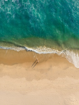 Draufsichtaufnahme von leuten, die auf varkala strand gehen