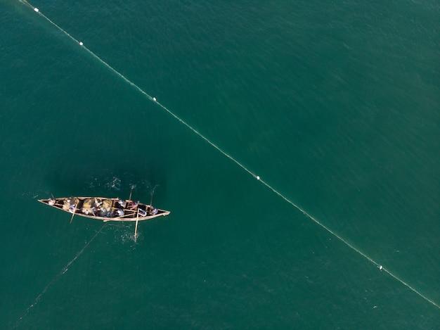 Draufsichtaufnahme von leuten in einem boot, das in varkala beach fischt