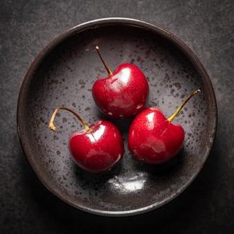 Draufsichtaufnahme von reifen roten süßkirschen in rostiger keramikplatte auf dunklem texturhintergrund, kirsche