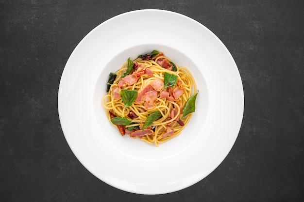 Draufsichtaufnahme von spaghetti-nudeln mit getrocknetem chili, knoblauch, süßem basilikum und speck in weißer keramikplatte auf dunklem texturhintergrund
