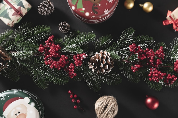 Draufsichtaufnahme von tannenzweigen mit kegel und geschenk auf einem schwarzen tisch - konzept von weihnachten