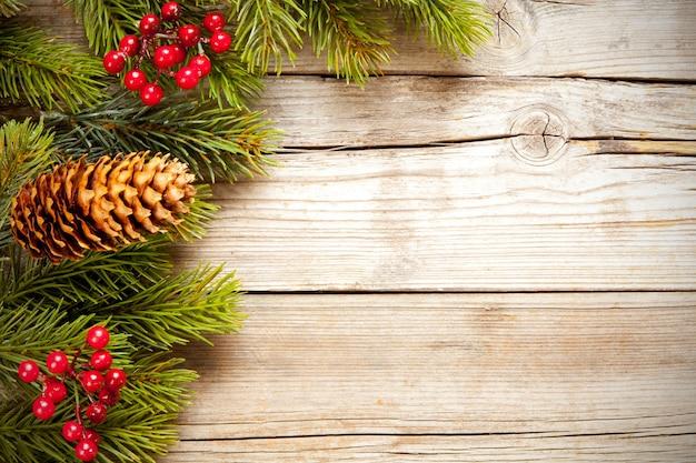 Draufsichtaufnahme von weihnachtsbaumzweigen mit mistel und einem tannenzapfen auf einer hölzernen oberfläche