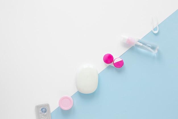 Draufsichtaugenpflegeprodukte auf zweifarbigem hintergrund