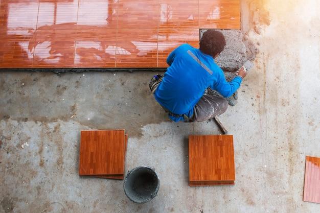 Draufsichtbauarbeiter, der fliese auf boden legt