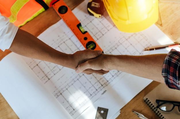 Draufsichtbauarbeiter-teamauftragnehmer-handerschütterung