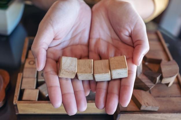 Draufsichtbild der frauenhände, die vier quadratische holzblöcke halten und zeigen