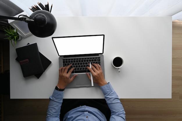 Draufsichtbild der geschäftsmannhand, die auf computer-laptop mit leerem bildschirm am schreibtisch mit büroausstattung tippt.