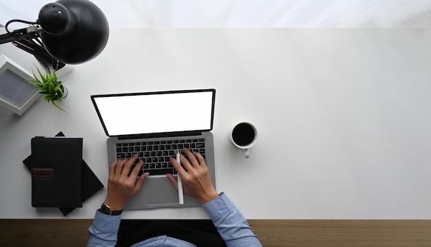 Draufsichtbild der geschäftsmannhand, die auf weißem computerbildschirm des leeren bildschirms am weißen arbeitstisch mit büroausstattung tippt.