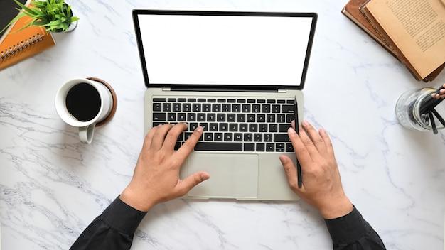 Draufsichtbild der hände des geschäftsmannes, die auf computer-laptop-tastatur mit weißem leerem bildschirm tippen, der auf marmorbeschaffenheitstabelle setzt, umgeben von kaffeetasse, stifthalter, topfpflanze und büchern.