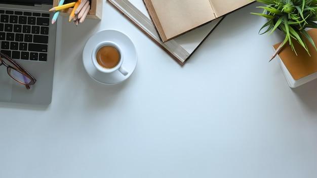 Draufsichtbild der heißen kaffeetasse, die auf weißen schreibtisch setzt, umgeben von computer-laptop, gläsern, büchern, topfpflanze, notiz und stifthalter. ordentliches arbeitsbereichskonzept.