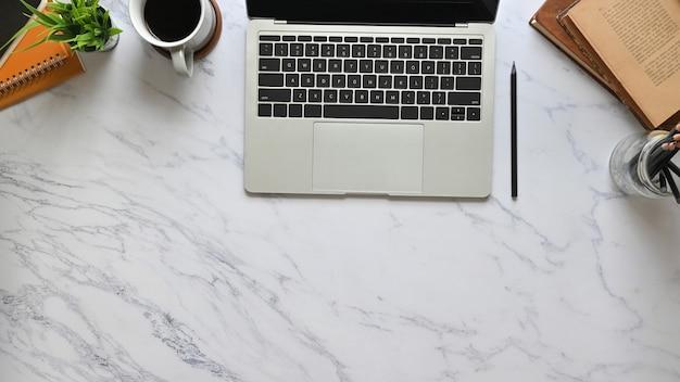 Draufsichtbild des computer-laptops, der auf marmorbeschaffenheitstabelle mit kaffeetasse, topfpflanze, büchern, bleistifthalter und stapel des notizbuchs setzt. ordentliches arbeitsplatzkonzept.