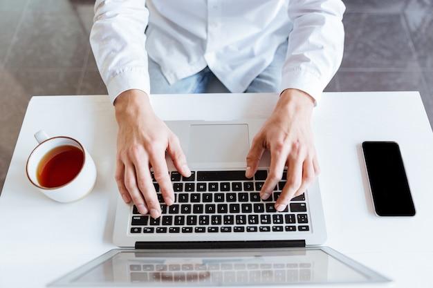 Draufsichtbild des mannes im weißen hemd mit laptop-computer gekleidet. coworking.