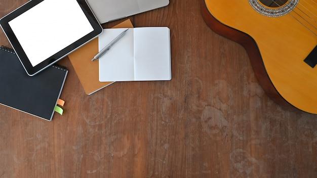 Draufsichtbild des musikerarbeitsplatzes. akustikgitarre, notizen, computertablett mit weißem leerem bildschirm, stift, der auf hölzernem schreibtisch zusammensetzt.