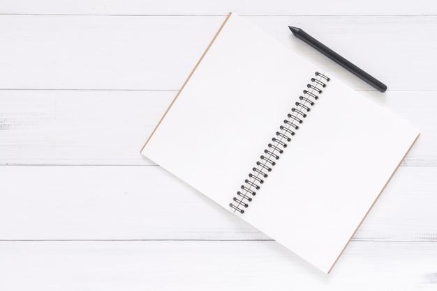 Draufsichtbild des offenen notizbuches mit leerseiten auf holztisch. bereit für das hinzufügen von text oder modell