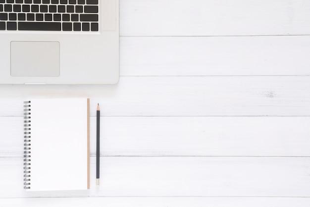 Draufsichtbild des offenen notizbuches mit leerseiten und des laptops auf holztisch