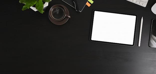 Draufsichtbild des weißen leeren bildschirmcomputertabletts und der büroausstattung setzen auf den schwarzen tisch.