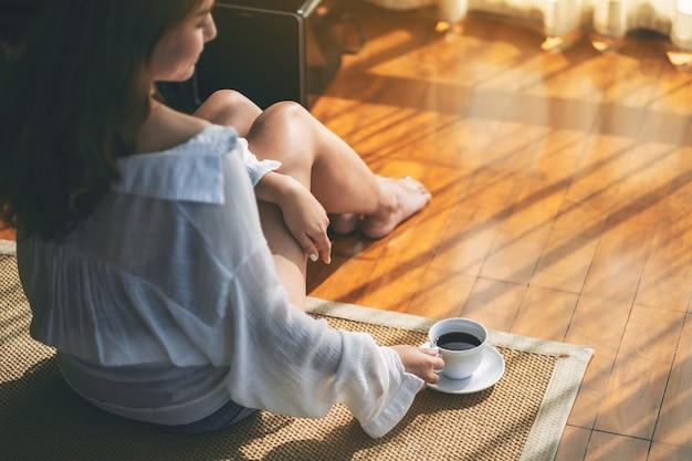 Draufsichtbild einer frau, die morgens eine tasse heißen kaffee auf dem boden sitzt und hält