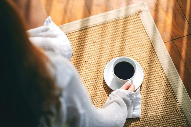 Draufsichtbild einer frau, die sitzt und eine tasse heißen kaffee auf dem boden am morgen hält