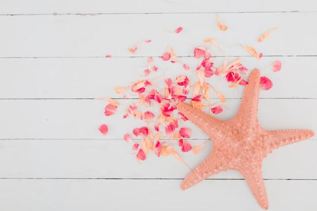 Draufsichtblumenblätter und -starfish auf hölzernem hintergrund