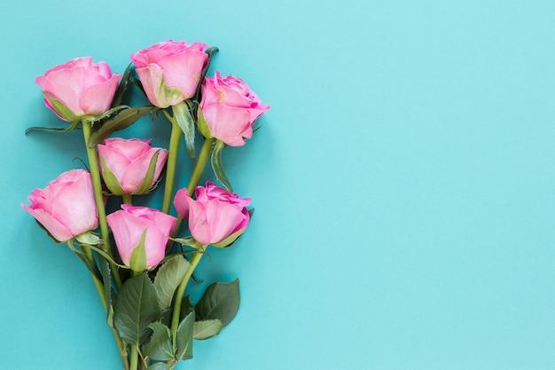 Draufsichtblumenstrauß von rosen auf blauem kopienraumhintergrund