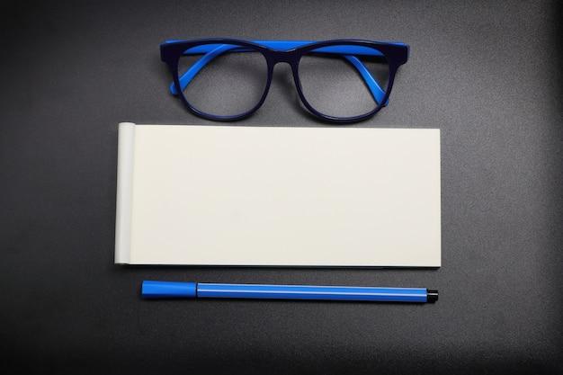 Draufsichtbriefpapier mit gläsern des blauen auges und blauem stift auf dunklem hintergrund
