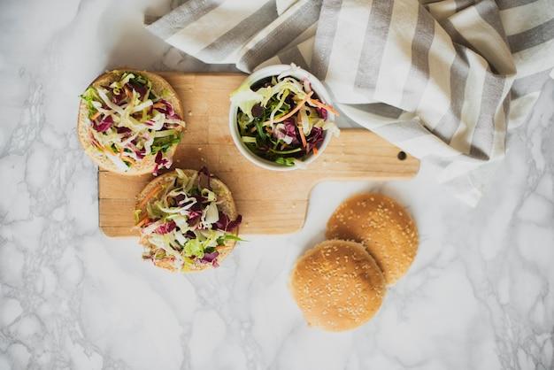Draufsichtbrötchen mit frischem salat auf tabelle